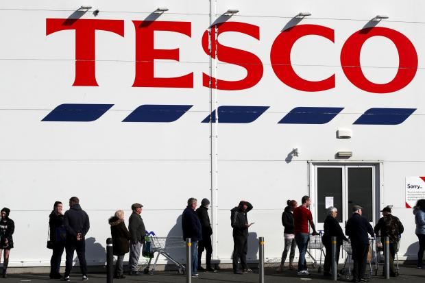 Braintree and Witham Times: People queue outside a Tesco Extra store in Madeley, Shropshire