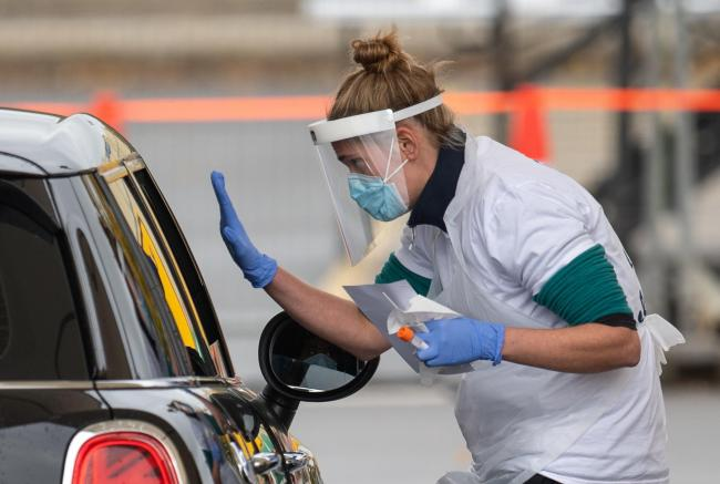 Staff collect samples at a drive through test centre. Picture: Joe Giddens/PA Wire