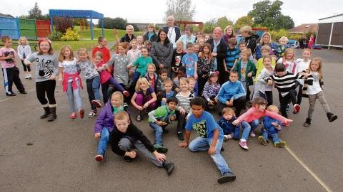 Pupils with staff, parents and Priti Patel