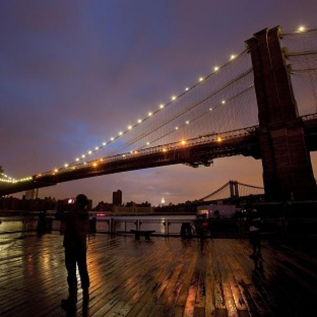 People stop along the waterfront in New York to photograph the Brooklyn Bridge and the Manhattan skyline (AP)