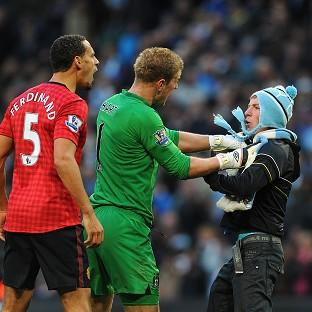 Manchester City goalkeeper Joe Hart holds back Matthew Stott as he goes towards Manchester United's Rio Ferdinand