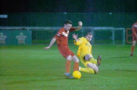 Witham's Lewis Godbold puts in a challenge during his team's game at Harlow Town. Picture courtesy of the Harlow Star