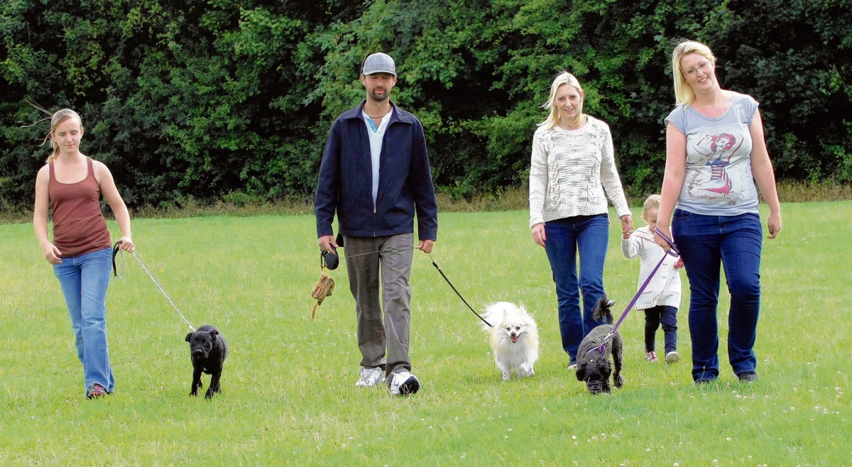 Dog walkers taking part in group walks in King George Playing Field of Cressing Road. Sarah Doyle with Oreo, Antony Dean with Gemma Hooker and Chloe Dean, 3,