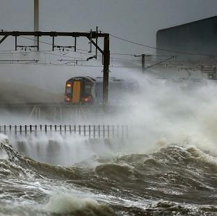 Braintree and Witham Times: A train is lashed by waves along the coast at Saltcoats as Scotland has been warned to expect a storm surge.