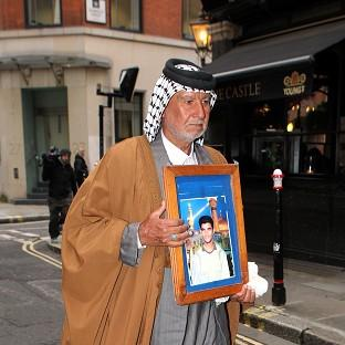 Braintree and Witham Times: Mizal Karim Al-Sweady, the father of Hamid Al-Sweady carries a photo of his son after leaving the inquiry into his death.