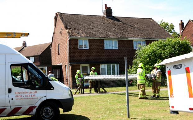 Emergency services work to make the house safe after it was struck by power cables