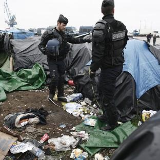 Braintree and Witham Times: Police officers take positions in a makeshift camp housing hundreds of illegal migrants from Syria, Afghanistan and Africa, after French authorities started to clear out camps in Calais