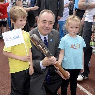 Braintree and Witham Times: Scotland's First Minister Alex Salmond with Craig Burns (aged seven) and Marilee Burns (aged five) and the Glasgow 2014 Queen's Baton at Meadowbank Stadium in Edinburgh. (Ben Birchall for Glasgow 2014)