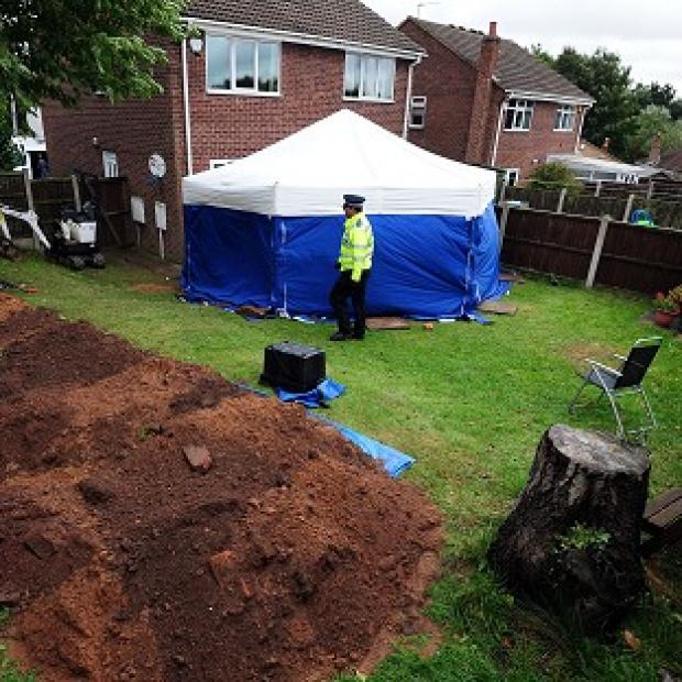 Braintree and Witham Times: Police in the garden of a house in Mansfield, where the remains of William and Patricia Wycherley were discovered