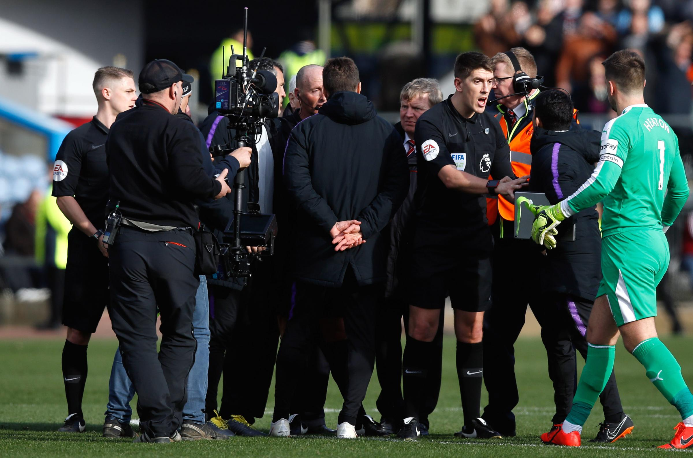 Tottenham Hotspur manager Mauricio Pochettino (centre) and his staff speak to referee Mike Dean and the match officials after their Premier League match at Turf Moor, Burnley. Picture: Martin Rickett/PA Wire